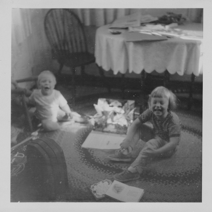 My brother David (18 months) and I (nearly 3) opening Christmas presents in 1963. The rug survived.